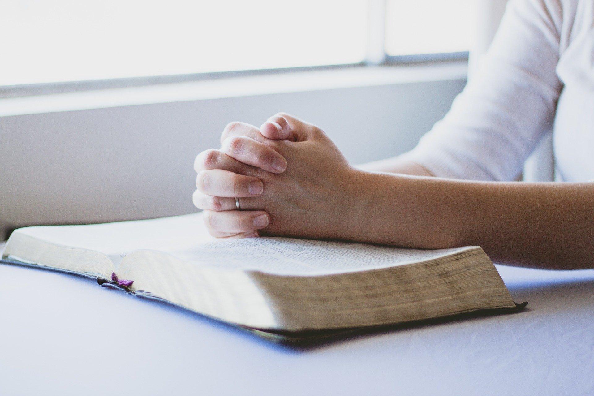 osszekulcsolt kezek biblia nyitott konyv